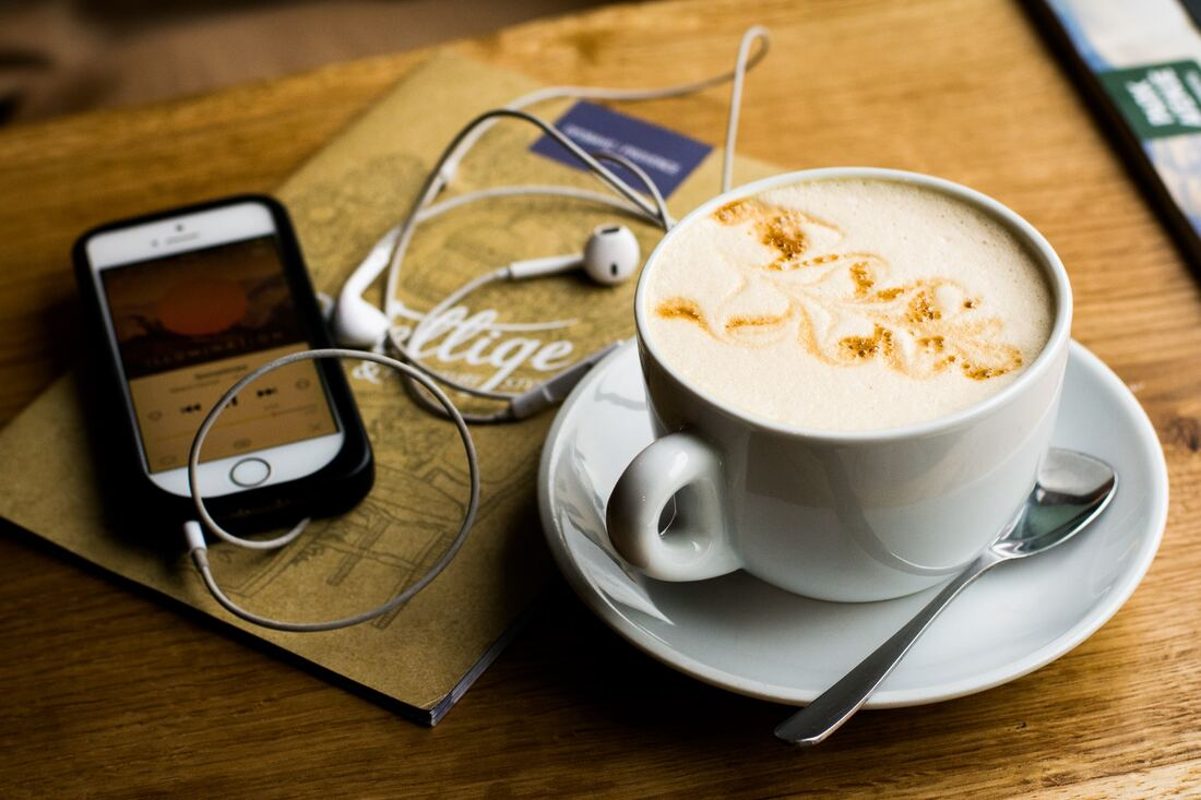 Phone playing podcast and coffee